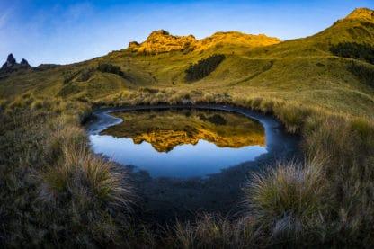 Schildvulkan in Papua-Neuguinea Mount Giluwe. Schöne Landschaft zwischen Vulkanen. Im Vordergrund hohes Gras, welches einen kleinen See umrandet. In dem See spiegeln sich die von der Sonne angestrahlten gelbgoldenen Berge und der blaue Himmel im Hintergrund. Landschaftsfotografie.