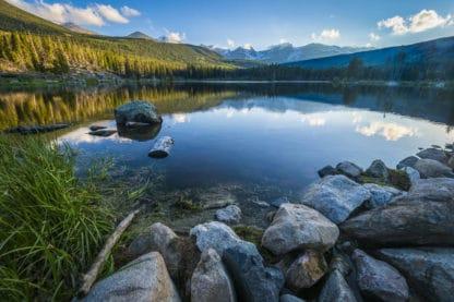 Rocky Mountains Sprague Lake, Colorado. Landschaftsfotografie. Steine und grünes Gras bilden das Ufer am vorderen Rande des Sees. Im See spiegeln sich der Wald, die Berge und der Himmel, die im Hintergrund liegen.