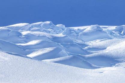 Schneelandschaft, Landschaftsfotografie. Zu sehen ist eine bergige weitreichende Landschaft vollständig mit Schnee bedeckt. Der Himmel ist durch und durch blau. Zwischen den Schneebergen bilden sich Schattenfelder, da die Landschaft von Links von der Sonne angestrahlt wird.