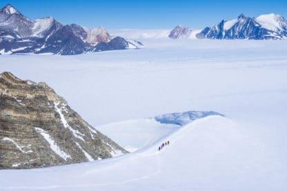 Landschaftsfotografie, Landschaftsbild Antarktis. Weitreichende Schneelandschaft, links ein brauner felsiger Berg, an seinem Fuß laufen fünf Personen durch den Schnee. Im Hintergrund weitere Berge, die teilweise mit Schnee bedeckt sind und der blaue Himmel.