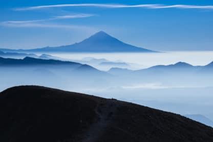 Blick von einem Berg auf den Popocatépetl Vulkan, Mexiko. Vor dem Vulkan liegen einige andere Berge, die zum Teil im weißen Wolkenmeer verschwinden. Der Himmel ist blau und gibt dem ganzen Bild eine blaue Grundstimmung.