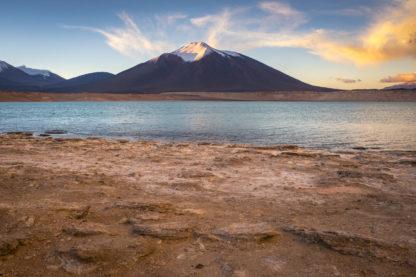 Ein Schneebedeckter Berg wird vom Abendlicht angestrahlt. Der Himmel ist blau und ein paar weiße Wolken werden teilweise orangerot von der Abendsonne angestrahlt. Im Vordergrund fließt ein Fluss zwischen steinigen Ufern entlang - Landschaftsfotografie