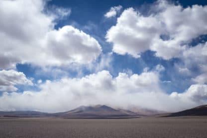 Zu sehen ist eine steinige Landschaft mit einigen Bergen im Hintergrund. Über ihnen eine mächtige Wolkenformation weißer Wolken vor dem blauen Hintergrund. Landschaftsfotografie.