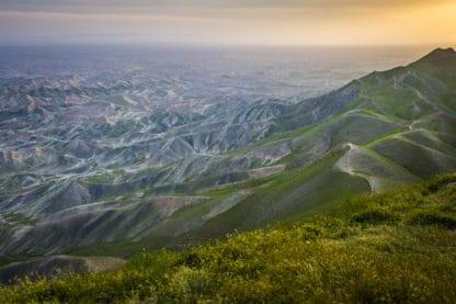 Berglandschaft Turkmen Sahra, Iran. Bergketten, teilweise grün bewachsen, der Beobachter steht auf einer grünen Wiese und schaut gen Tal. Abendsonne, Abendlicht. Landschaftsfotografie.