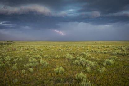 Landschaftsbild aus Limon in Colorado, Sturm mit dunklem Himmel, Blitz und schwarzen Wolken über einer Wiese.