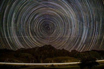 Startrails, ISS, Meteorit und ÖBB. Die weißen Startrails sind vor dem Hintergrund des schwarzen Himmels zu sehen. Die ISS und ein Meteorit bilden eine weiße Spur. Unterhalb liegen Berge und Wälder. Im Vordergrund fährt ein Zug der ÖBB der in seinem weißen Licht heraussticht.