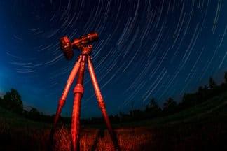 Startrails mit Leofoto Stativ und Olympus M1X. Der Himmel ist dunkelblau. Das Stativ und die Kamera werden von einem roten Licht angestrahlt.