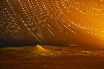 Zu sehen ist eine sandige Landschaft, ein kleiner Hügel und darüber ein Sternenhimmel als Startrails fotografiert mit einer langen Belichtungszeit. Das Bild ist von einem orangeroten Licht geprägt.
