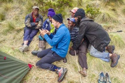 Einige Personen sitzen neben einem Zelt im Gras und schauen gemeinsam auf ein Mobiltelefon, auf dem sie sich anscheinend Bilder anschauen. Reisefotografie.