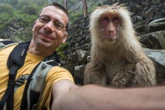 Adrian Rohnfelder nimmt ein Selfie mit einem Affen auf. Im Hintergrund eine Steinmauer. Der Fotograf lächelt, der Affe hat ein ausdrucksloses Gesicht. Reisefotografie.
