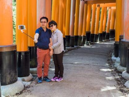 Torii Tunnel in Fushimi (Kyoto) in Japan. Zwei Personen nehmen ein Selfie auf. Reisefotografie.