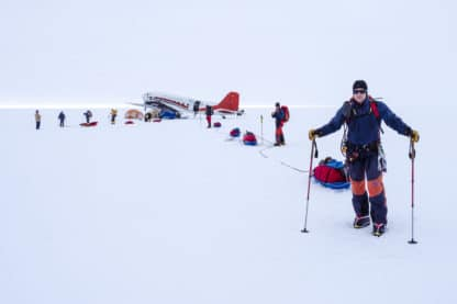 Eine weitreichende Schneelandschaft. Im Hintergrund ist ein Flugzeug zu sehen. Einige Menschen bereiten sich auf eine Expedition vor und sind vollkommen ausgerüstet mit Schneemontour, Schneeschuhen, Wanderstöcken und weiterem Gepäck. Reisefotografie.