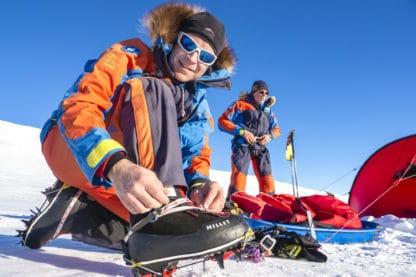 Zwei Personen sind ausgerüstet für eine Expedition durch den Schnee. Die Person im Vordergrund zieht sich Schneeschuhe mit Spikes an. Im Hintergrund ein Zelt und weitere Ausrüstung. Reisefotografie