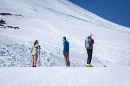 Drei Personen stehen an einem schneebedeckten Hang. Eine der Personen trägt Unterwäsche und in der Hand Wanderstöcke. Die anderen beiden sind vollständig bekleidet. Reisefotografie