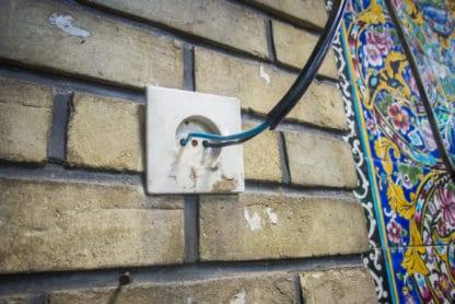 Zu sehen ist eine Wand, teils gekachelt, mit einer Steckdose. In die Steckdose ist direkt ein Kabel mit seinen zwei Kontakten eingesteckt. Iran, Reisefotografie.