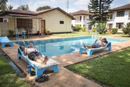 Zwei Personen liegen an einem Pool auf Sonnenliegen. Beide lesen ein Buch. Ringsherum ist eine Wiese, es stehen Häuser dort und ein Baum. Reisefotografie.