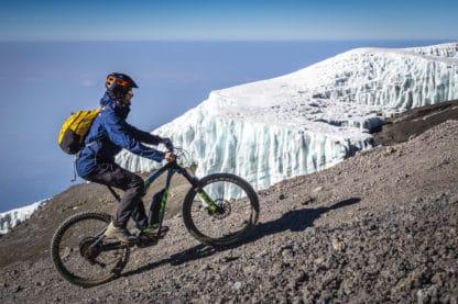 Ein Fahrradfahrer fährt mit einem Mountainbike auf 5.800m am Gletscher vorbei. Er fährt auf Stein, im Hintergrund ist ein Gletscher zu sehen und der blaue Himmel. Reisefotografie.