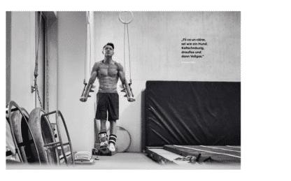"""Spitzensportler Andreas Toba in einer Turnhalle. Turner mit verletztem Bein. Neben ihm Turnmatten. Schwarz-Weiß-Bild aus dem Buch """"GER - many are one."""""""